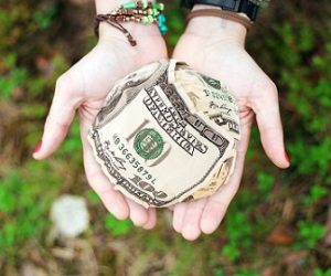 Woman holding ball od 100 dollar bills in her hands