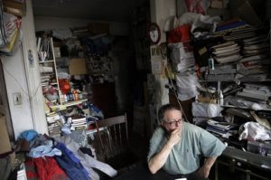 Man sitting in a cluttered room