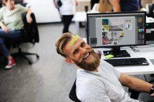 """Young man with a beard smiling at his work desk with """"be happy"""" written on his forehead"""