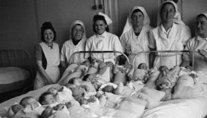 Nurses standing around many babies on a hospital bed in WW2